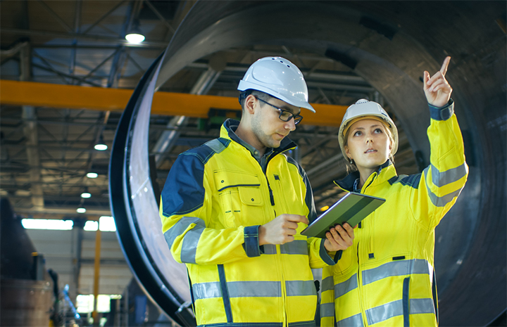 Two-people-in-helmets-in-industrial-environment-720x465