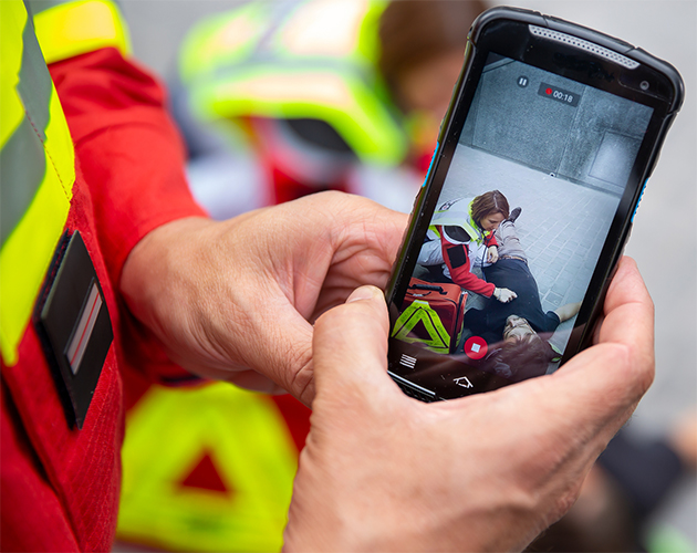 Paramedic-holding-smartphone-with-Agnet-and-video-630x500
