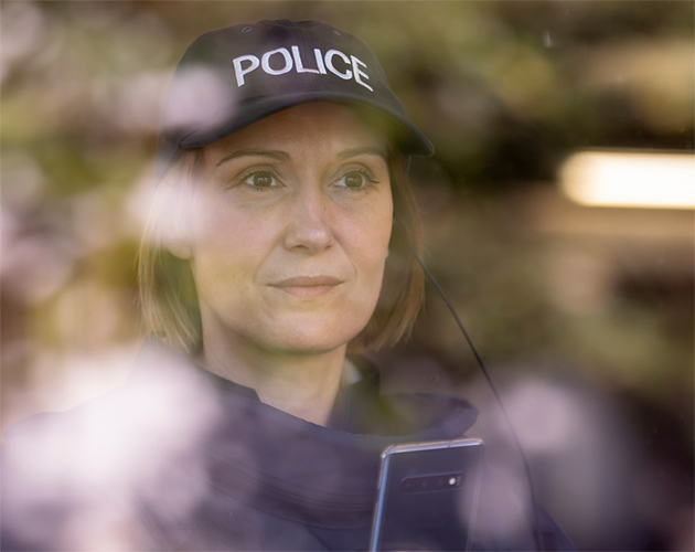 Police-officer-behind-a-window-with-reflections-630x500