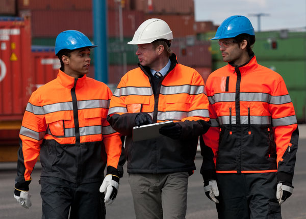Three people in hard hats, walking and discussing. Containers on the background.