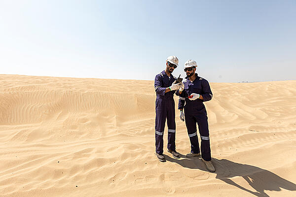 Two men in helmets in the desert, looking at a smart device