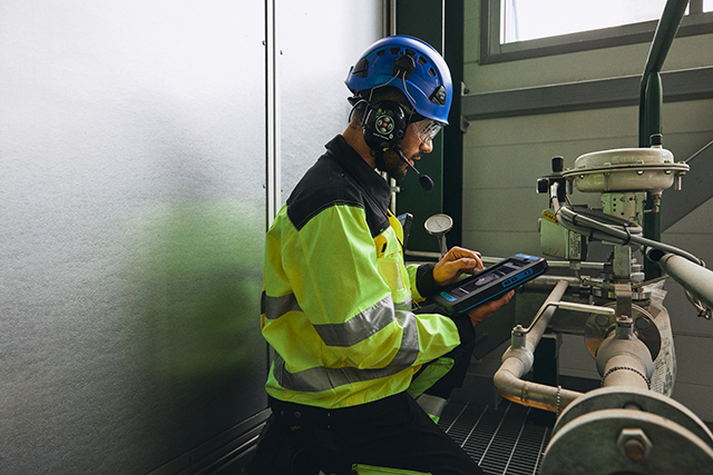 Worker-with-smart-device-next-to-factory-equipment-640px-wide