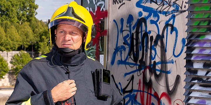 Firefighter carrying Tactilon Dabat in a carrying solution, graffiti on the background