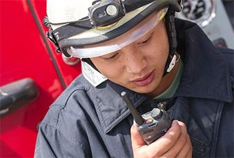 Firefighter talks into his TETRA radio
