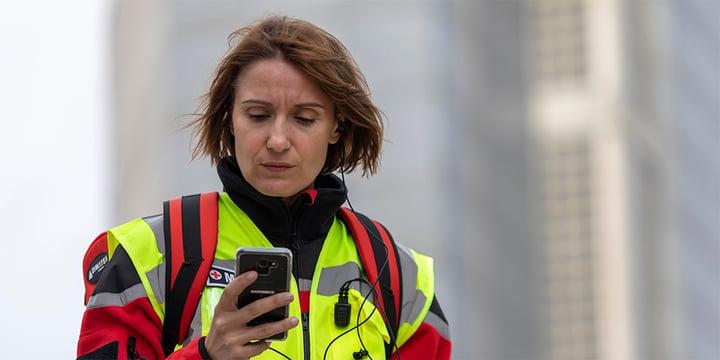 Paramedic/nurse uses a push to talk app on a smartphone