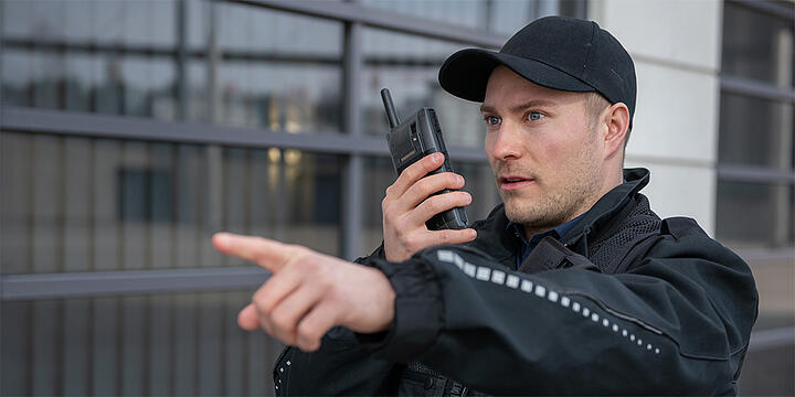 Security professional with Tactilon Dabat hybrid device, points with finger