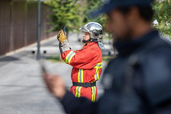 Fireman is taking a photo, a police out of focus is on the foreground
