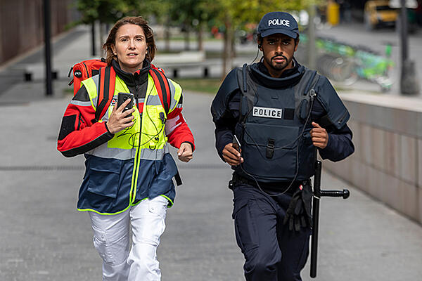 Medical professional with a smartphone and police, running