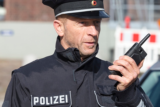 Police holding a dual-mode device for TETRA and broadband