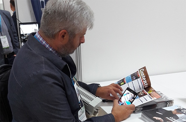 Visitor browsing a Key Touch magazine at RadioExpo Poland