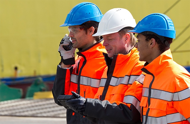 Three workers, one using TETRA radio