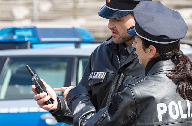 Two police officers look at Tactilon Dabat smart device