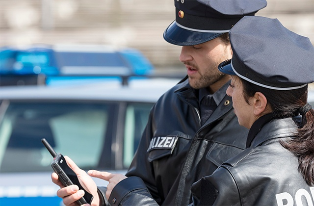 Two police officers looking at Tactilon Dabat display