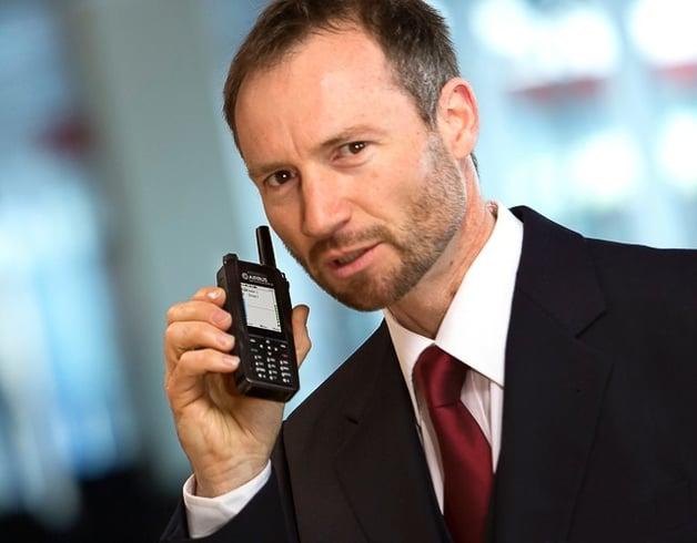 Man on an airport holding a TH1n TETRA radio