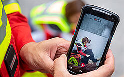 Rescue worker holding a smartphone which has video on screen