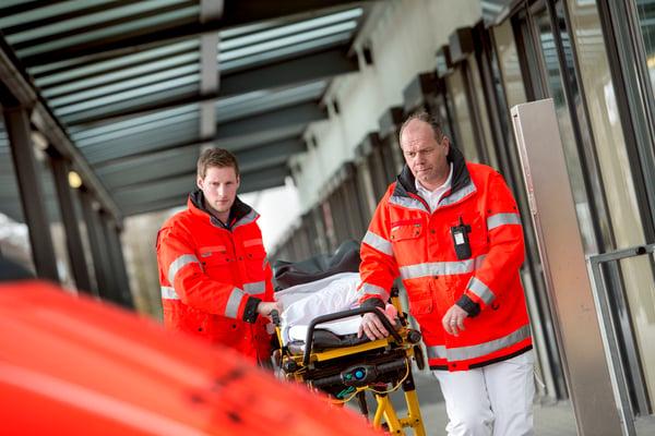 Two paramedics are pulling a gurney towards an ambulance